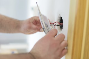 Handy man installing light switch after home renovation